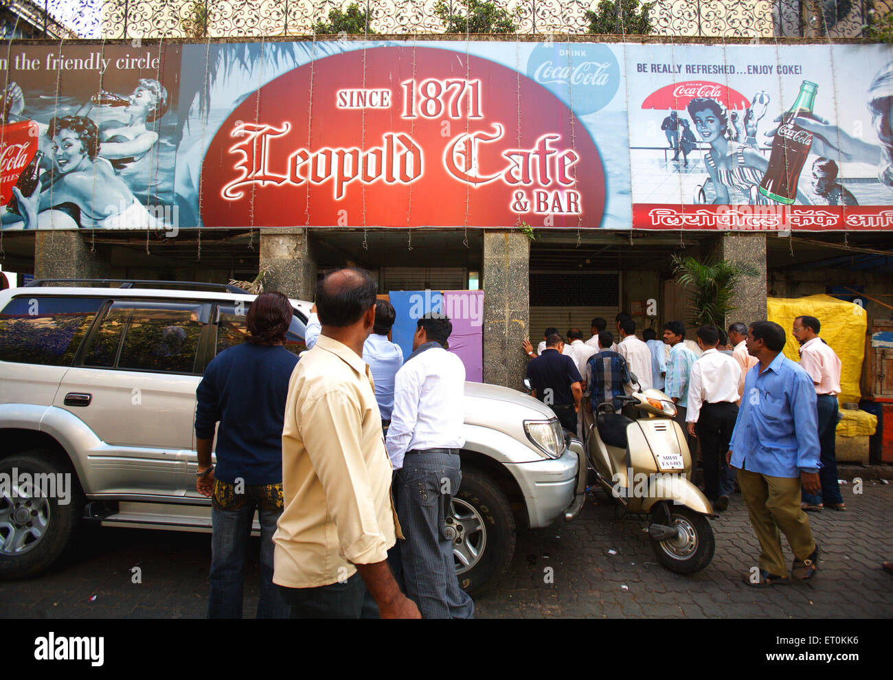 Onlookers looking at losses done to Leopold Caf' after terrorist attack by Deccan Mujahedeen in Colaba ; Bombay - Stock Image