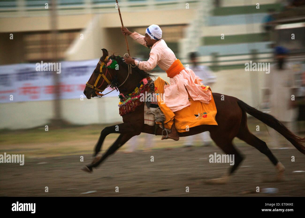 Nihang Sikh warrior performing stunts ;celebrations Consecration perpetual Sikh Guru Granth Khalsa Sports ground - Stock Image