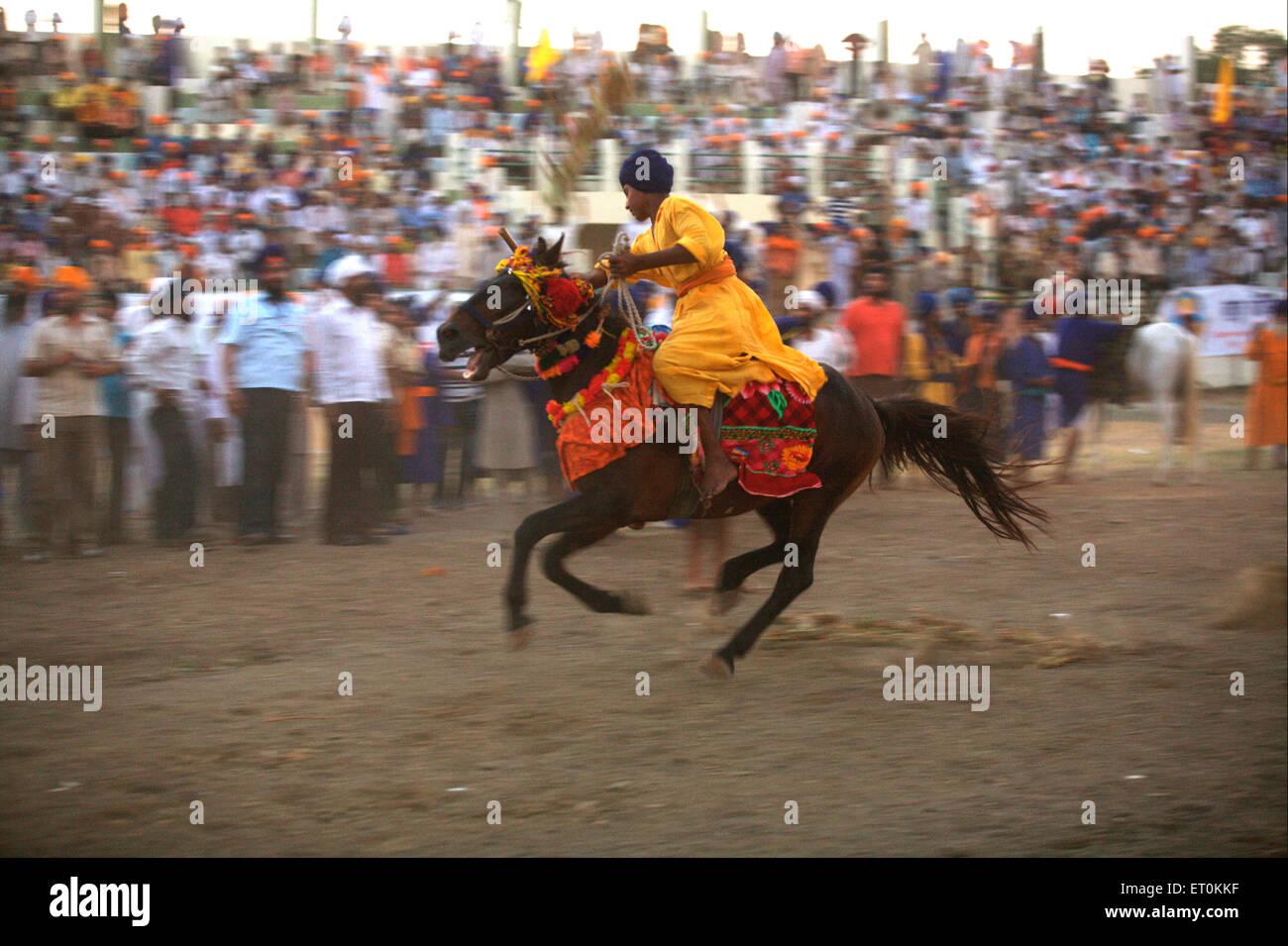 Nihang Sikh warrior performing stunts ; event onsecration of perpetual Guru of Sikh Guru Granth at Khalsa Sports - Stock Image