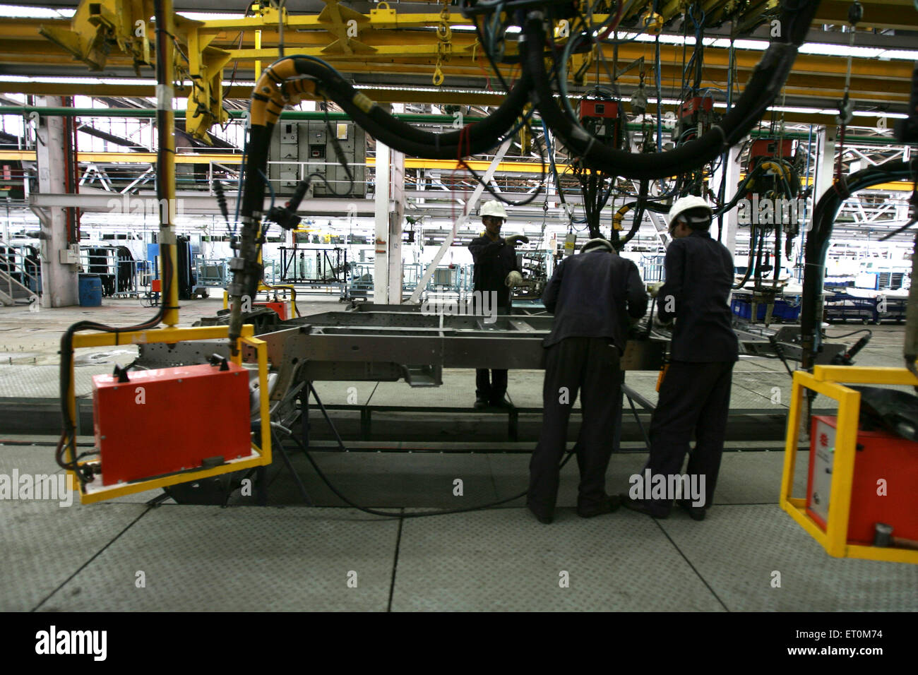 Automobile experts working in workshop ; Tata motors plant ; Pimpri near Pune ; Maharashtra ; India - Stock Image