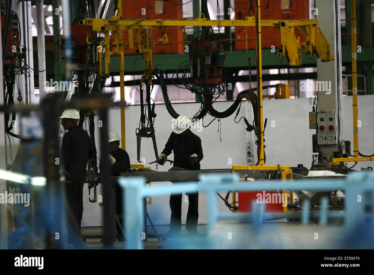 Automobile experts working on body of vehicles in workshop ; Tata motors plant ; Pimpri near Pune ; Maharashtra - Stock Image