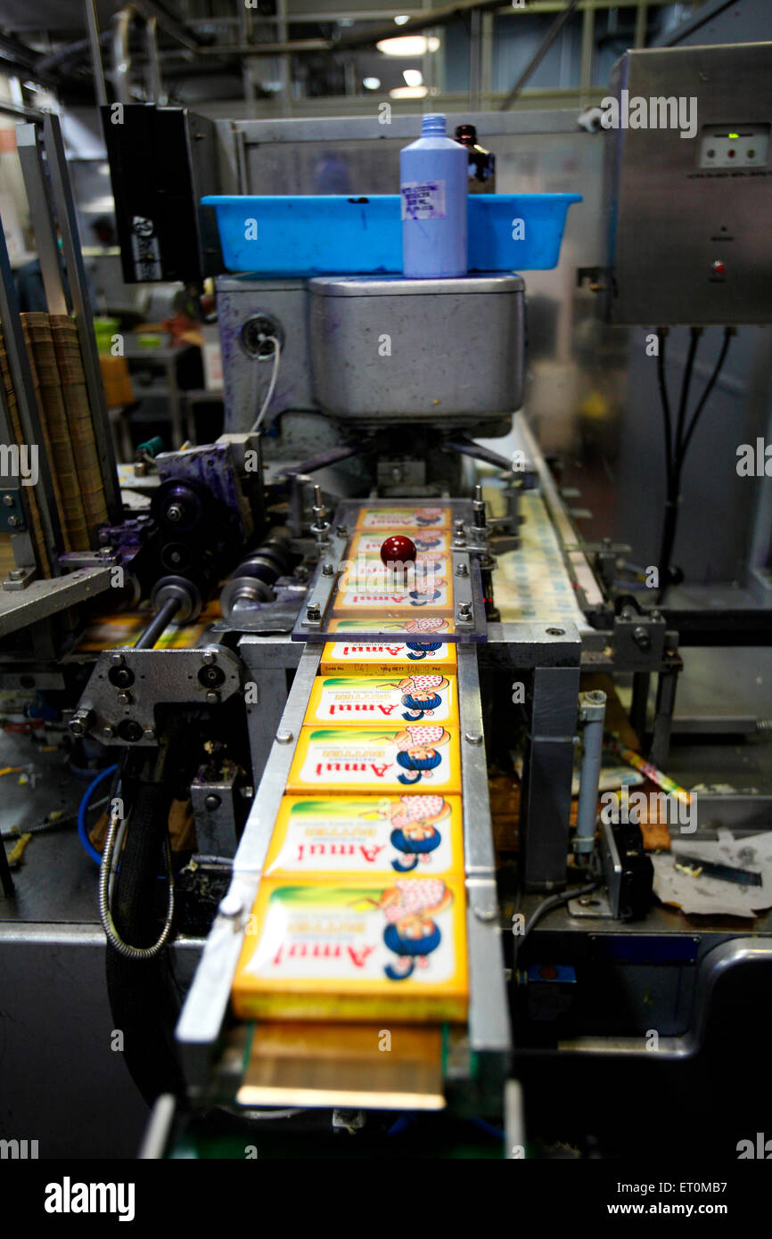 Packed Amul butter in wrappers coming out in Amul factory in Anand ; Gujarat ; India - Stock Image