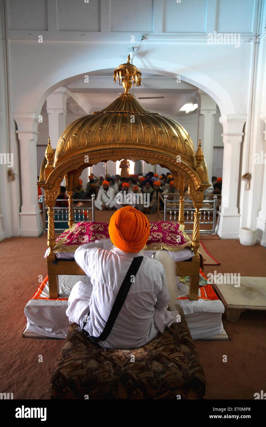 Sikh cleric waves whisk over holy Guru Granth Sahib in Anandpur Sahib Gurudwara in Rupnagar district ; Punjab ; - Stock Image