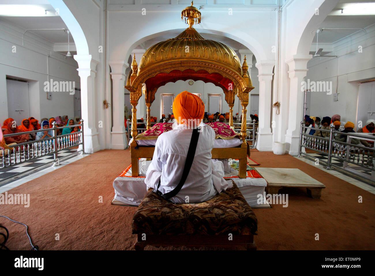 Sikh cleric waves whisk over holy Guru Granth Sahib at the Anandpur Sahib Gurudwara in Rupnagar district ; Punjab - Stock Image