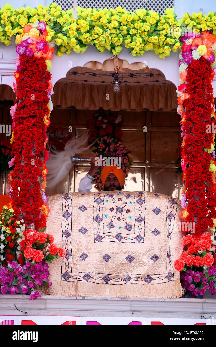 Sikh cleric waves a whisk during Hola Mohalla  festival at Anandpur Sahib Gurudwara in Rupnagar district ; Punjab - Stock Image
