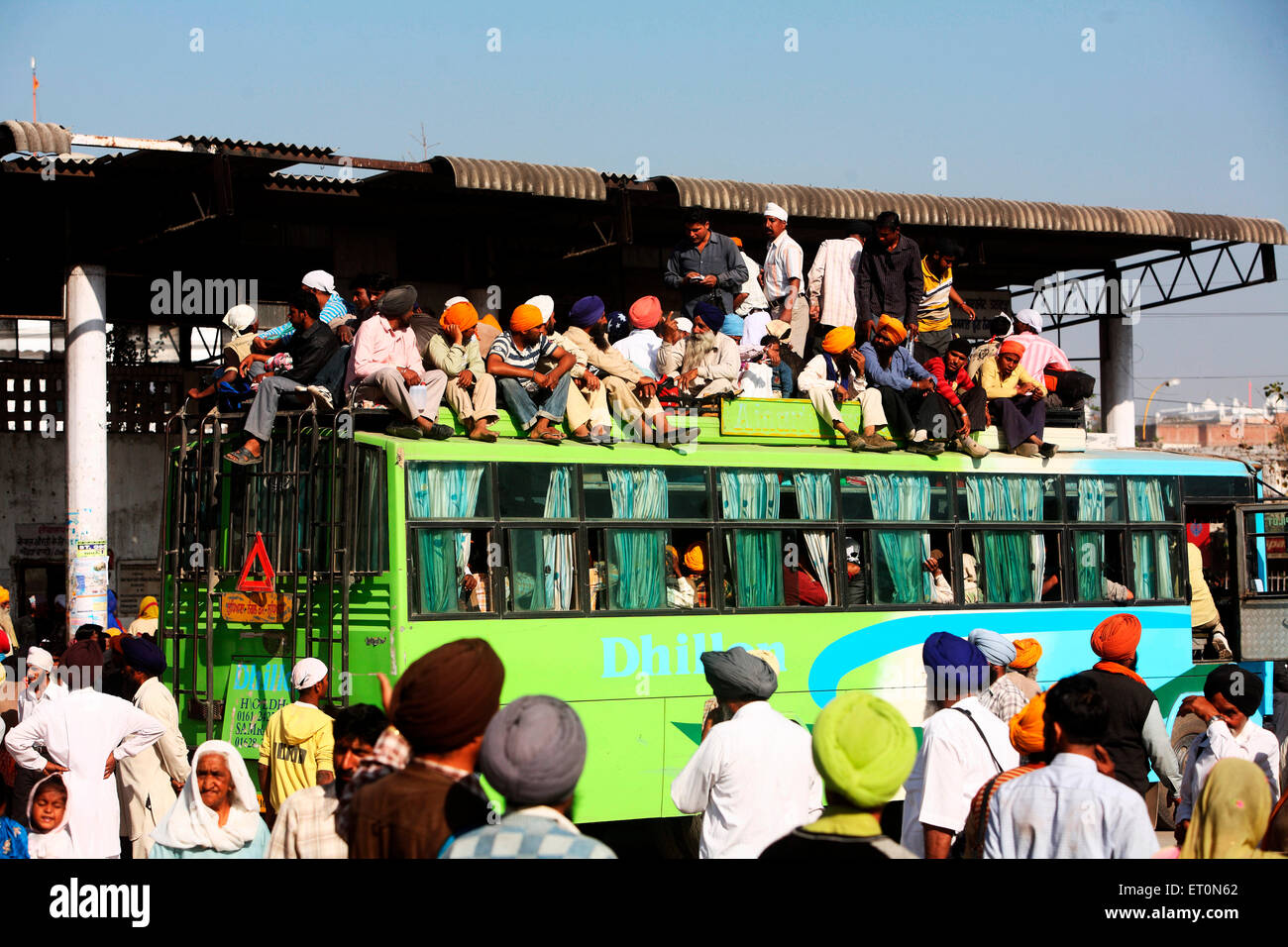 People travelling on rooftop of bus in Punjab ; India - Stock Image
