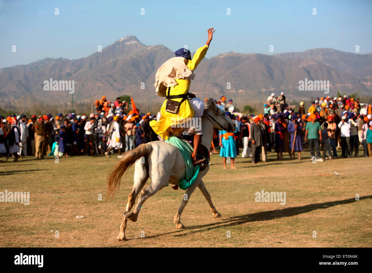 Nihang or Sikh warrior performing stunts riding on horse during Hola Mohalla festival at Anandpur sahib - Stock Image
