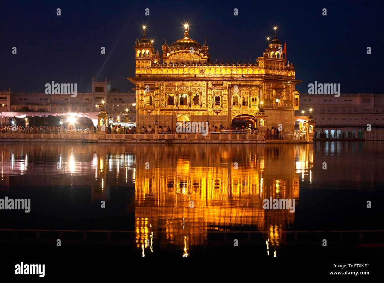 Glow of Harmandir Sahib or Darbar Sahib or Golden temple reflection in lake in Amritsar; Punjab ; India - Stock Image
