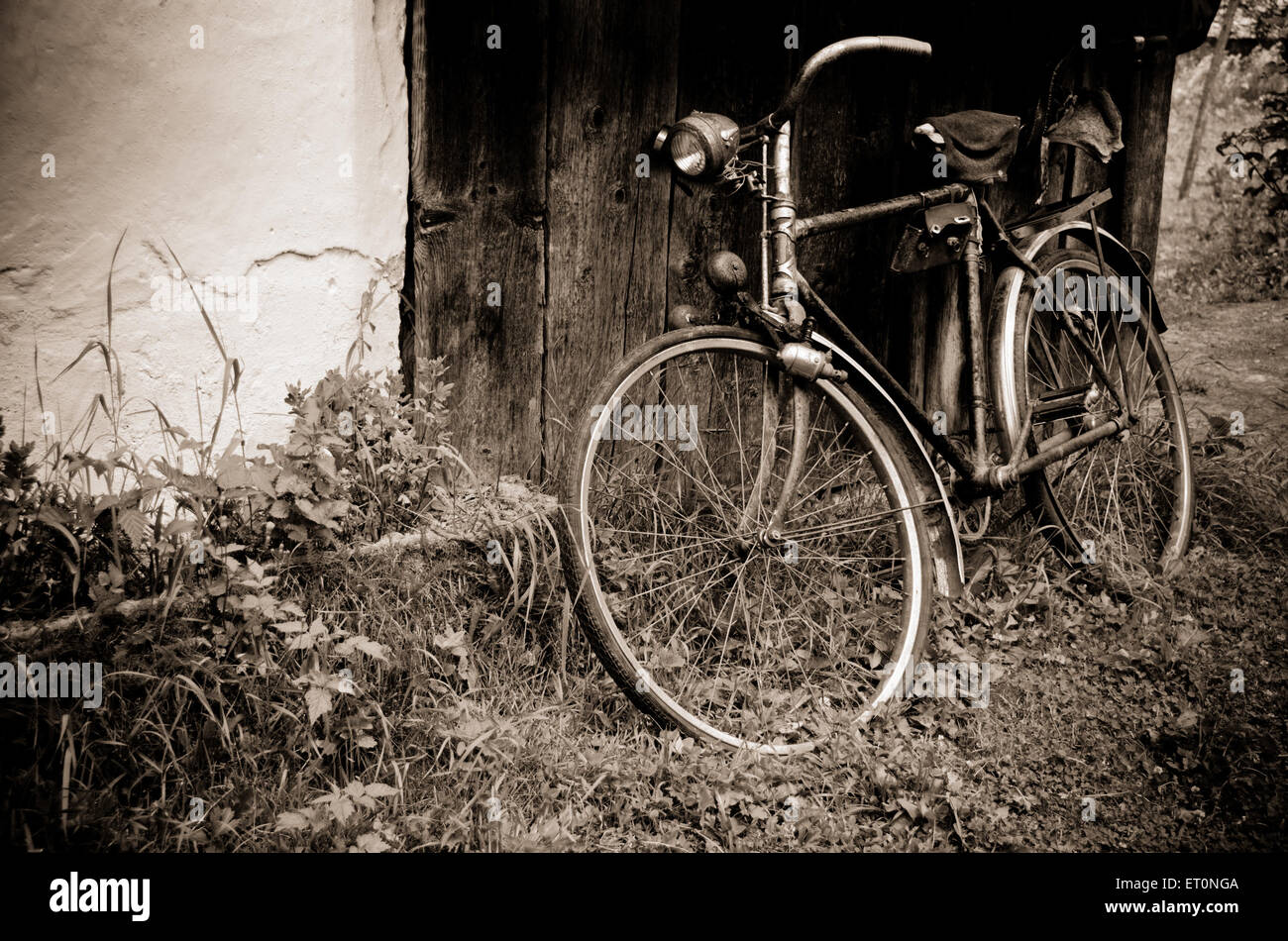 Old bicycle near the house in the village - Stock Image