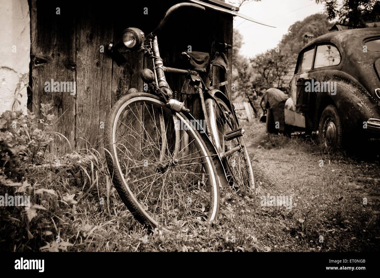 Old sepia vintage retro car and bicycle in the village - Stock Image