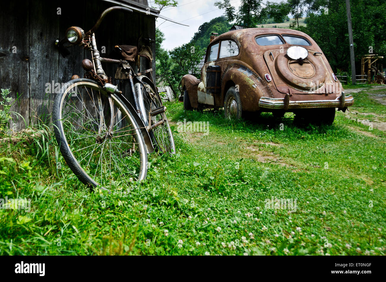 Old vintage car and bicycle in the village -nostalgic concept - Stock Image