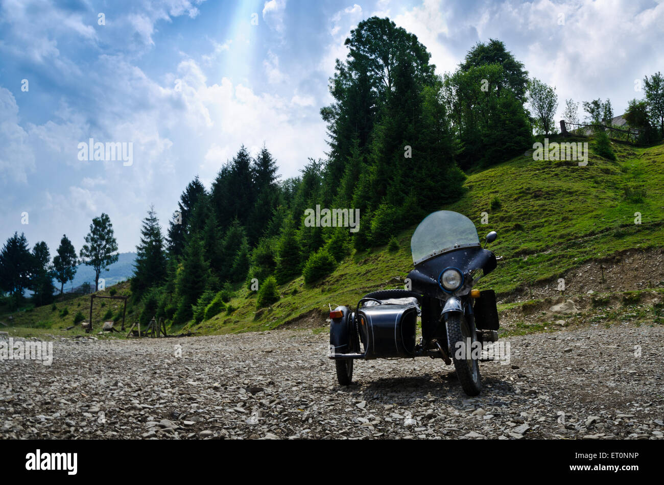 Old motorcycle - retro motobike at the pines and skyes background - Stock Image
