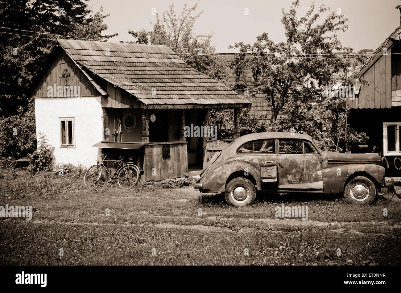 Old retro rusty vintage car and old house - Stock Image