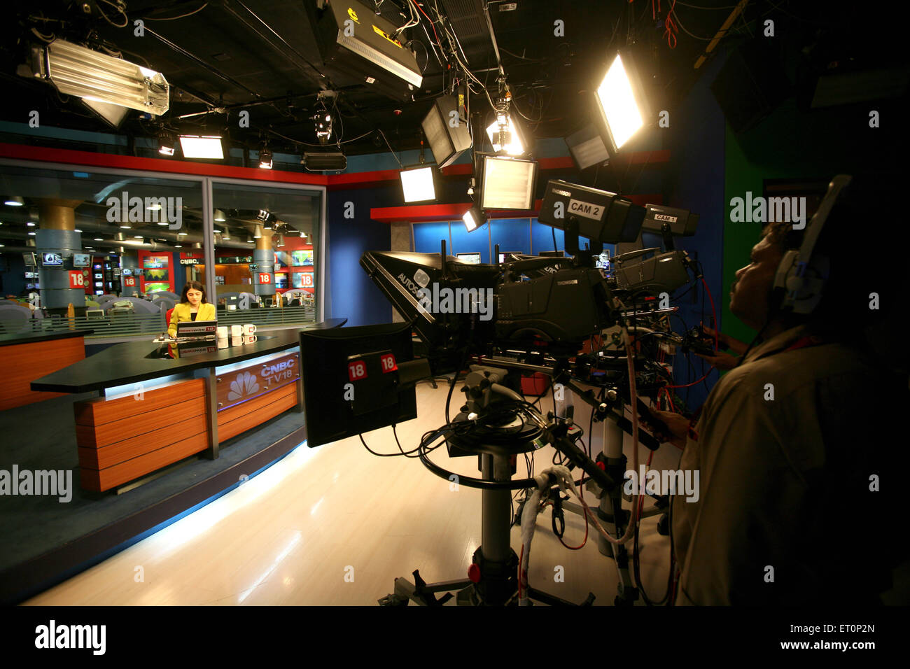 Cameraman shooting anchor with news in newsroom of cnbc channel ; Bombay Mumbai ; Maharashtra ; India - Stock Image