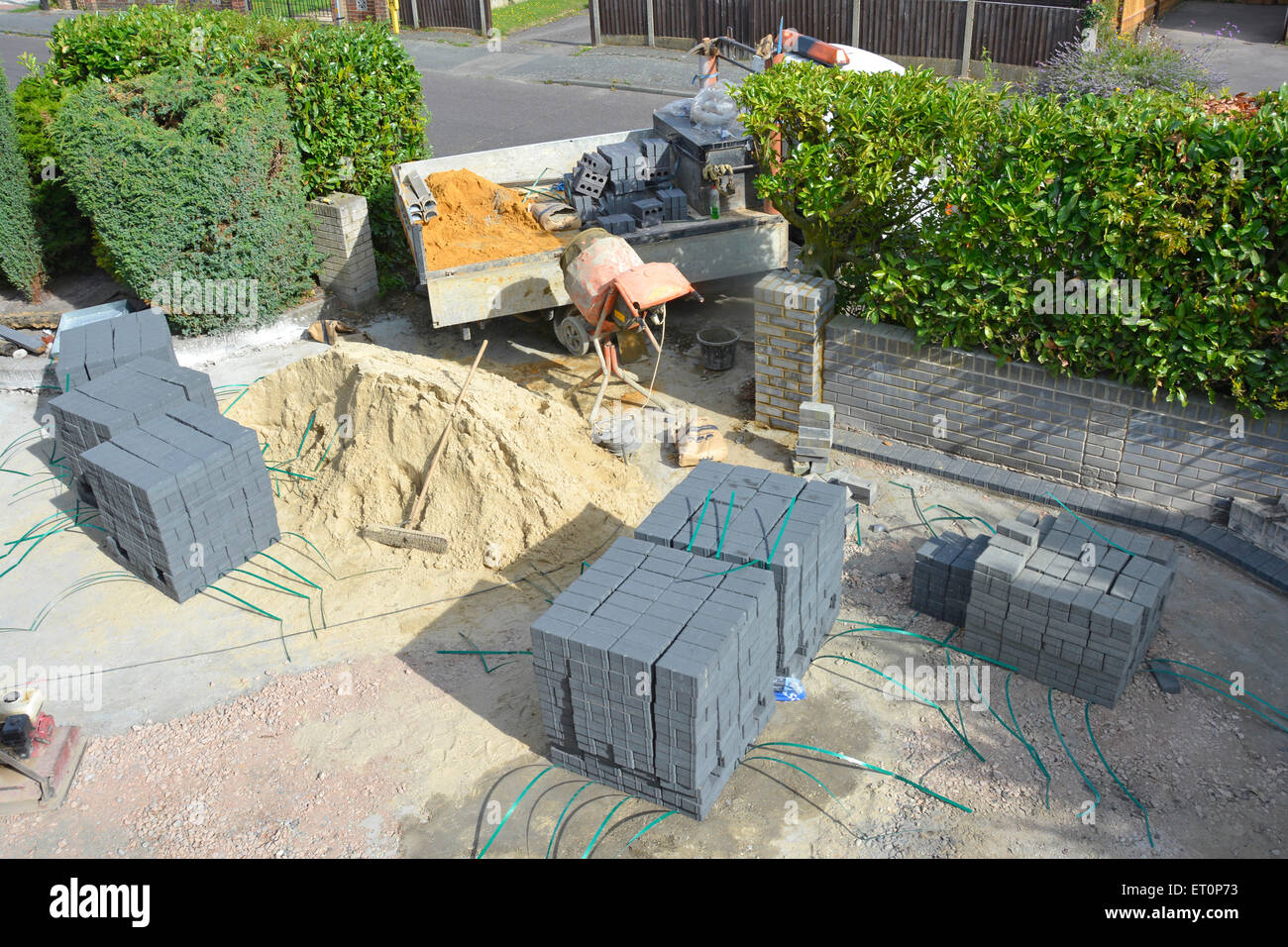 Sand and paving blocks in front garden of residential property creating a new car driveway after removal of old Stock Photo