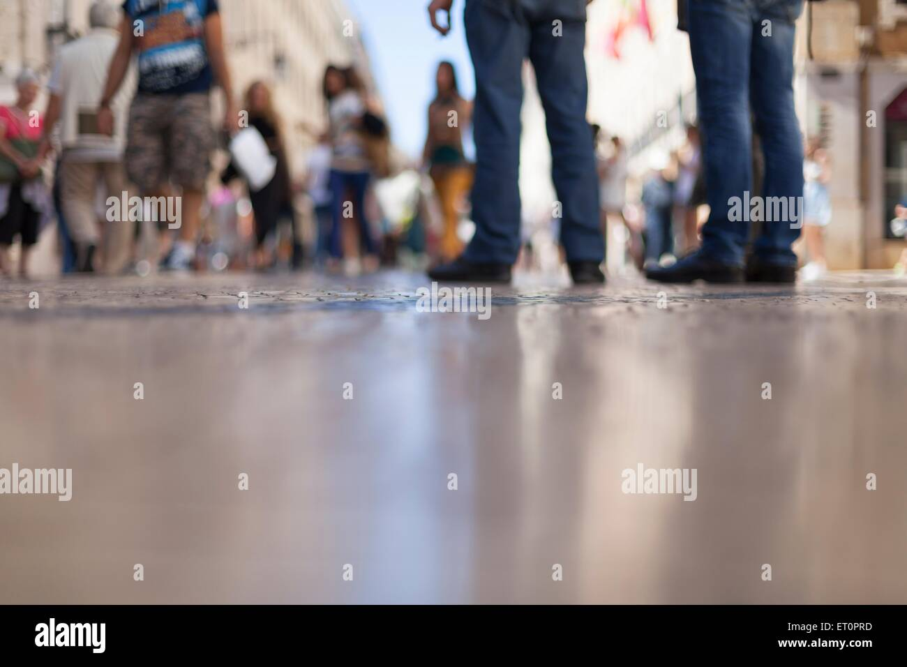 Blurry image of people on the street, ground view - Stock Image
