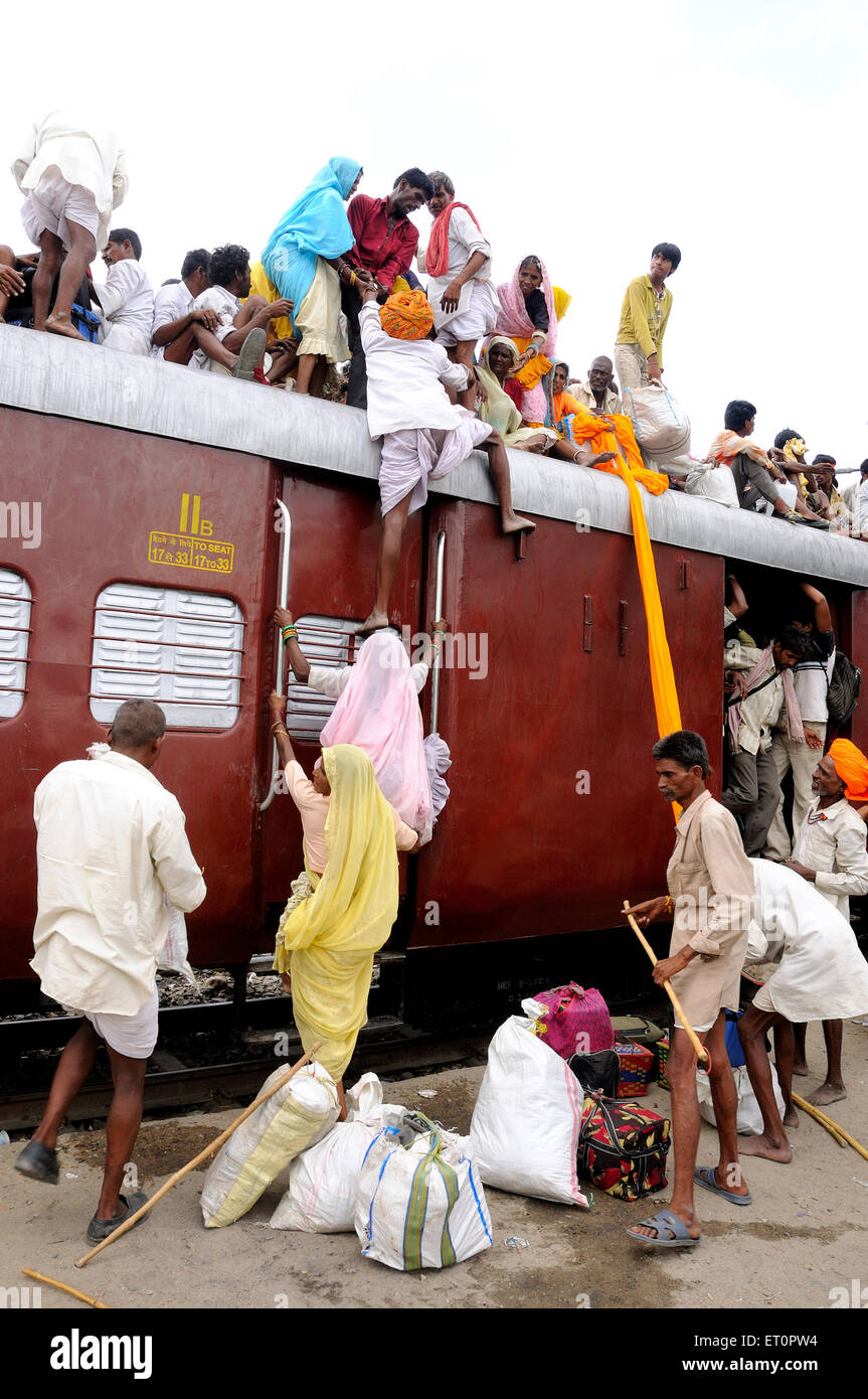 People climbing on roof of train for risky travel ; Marwar railway station ; Rajasthan ; India - Stock Image