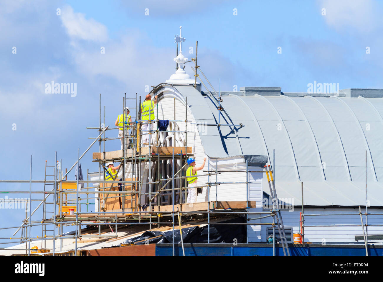 Building decorators put finishing coats of paint on Cleethorpes Pier. - Stock Image