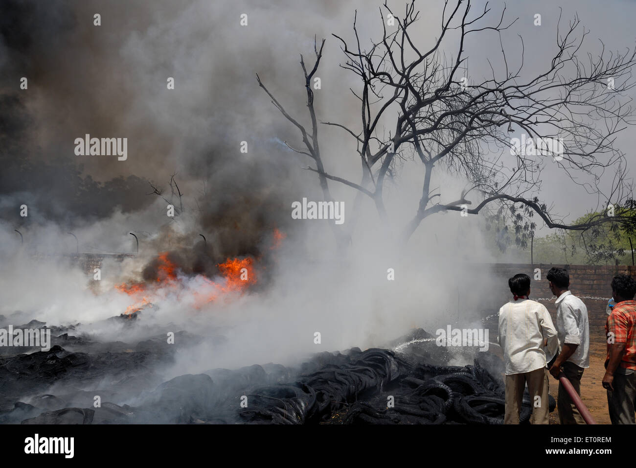 Firemen trying to douse off fire while scrap warehouse ; Jodhpur ; Rajasthan ; India - Stock Image