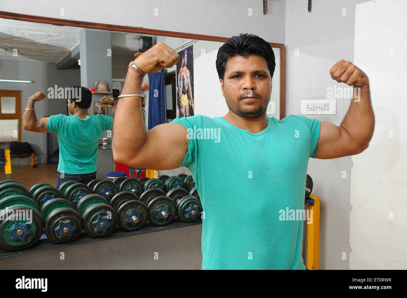 Man showing biceps in fitness centre MR#786 - Stock Image