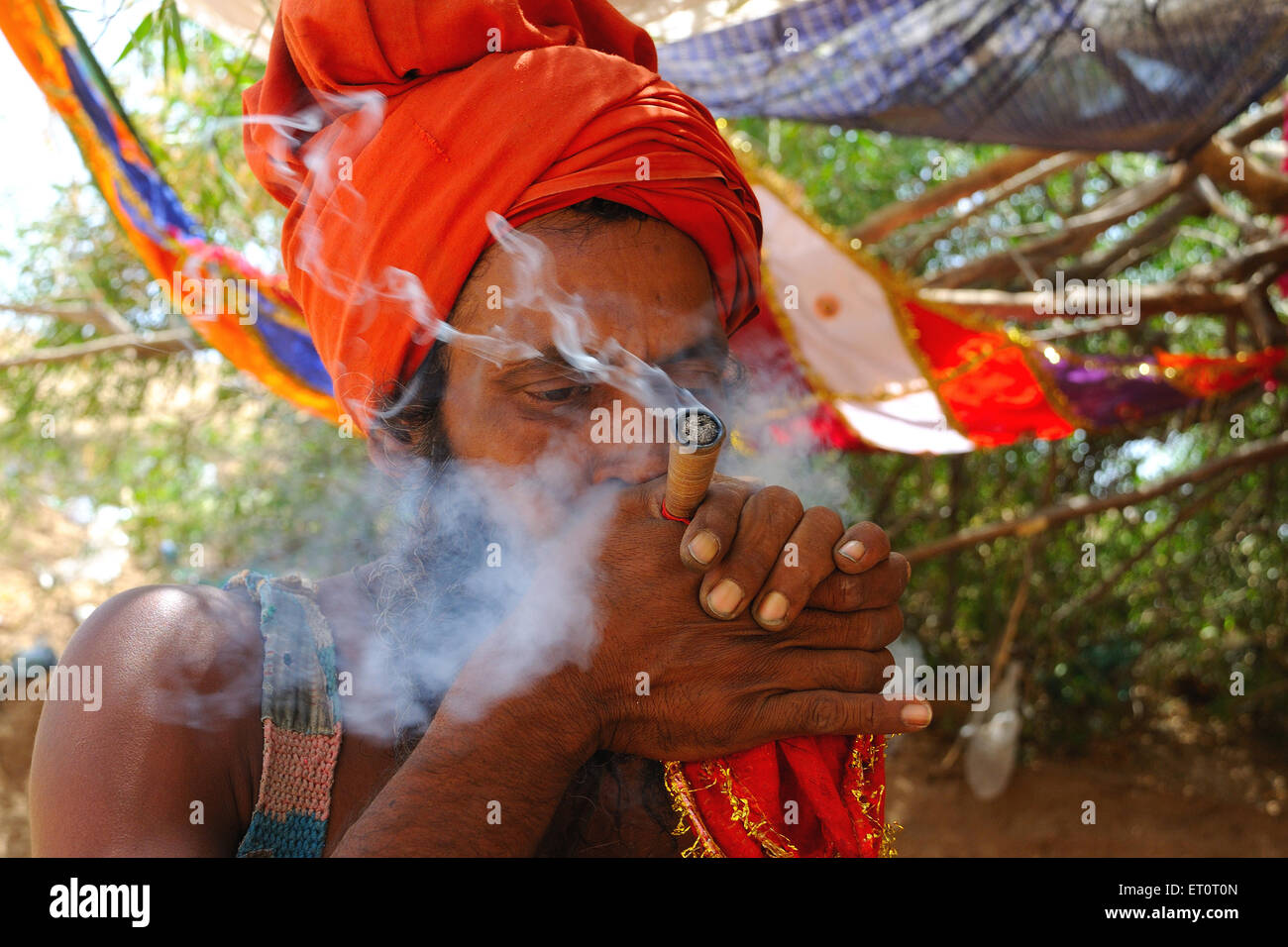Priest smoking chillum NOMR - Stock Image