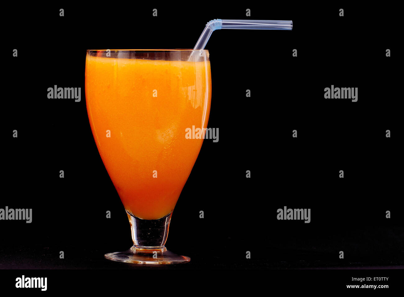 Orange juice in glass on black background - Stock Image