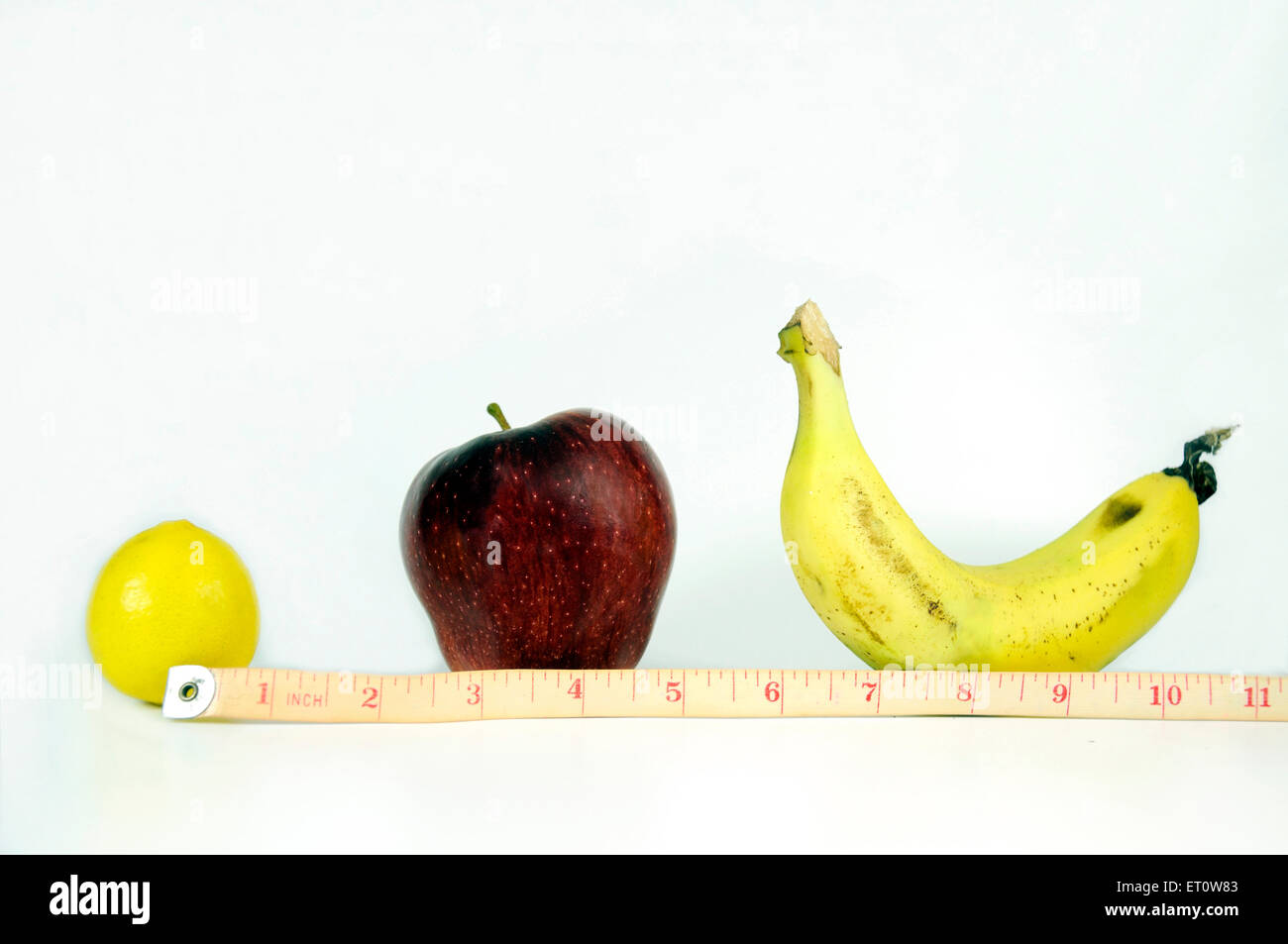 Measuring tape showing inches lemon apple banana on white background India Asia - Stock Image