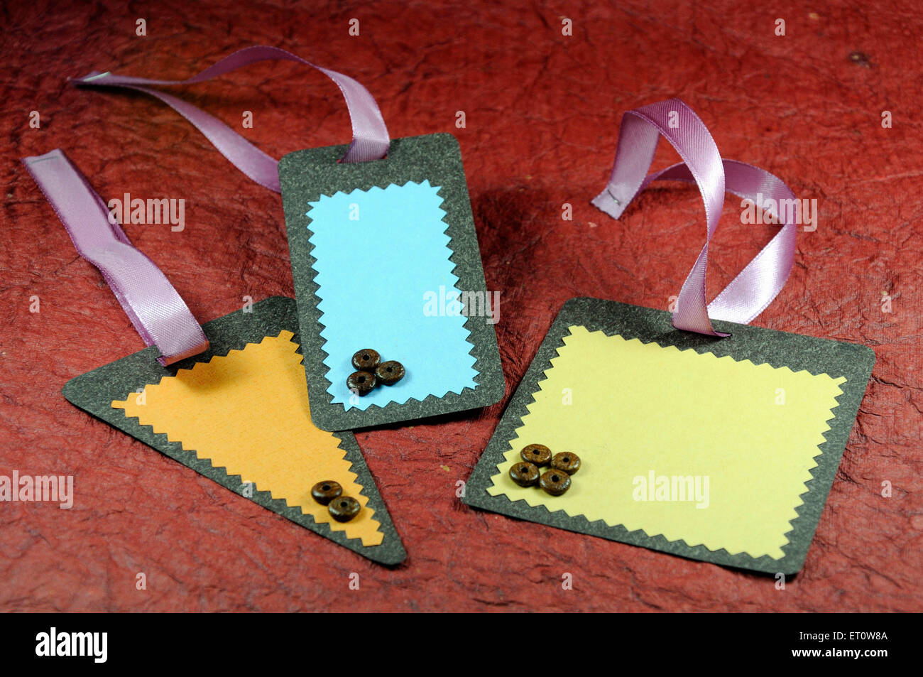 Different shapes of labels on maroon background India Asia - Stock Image