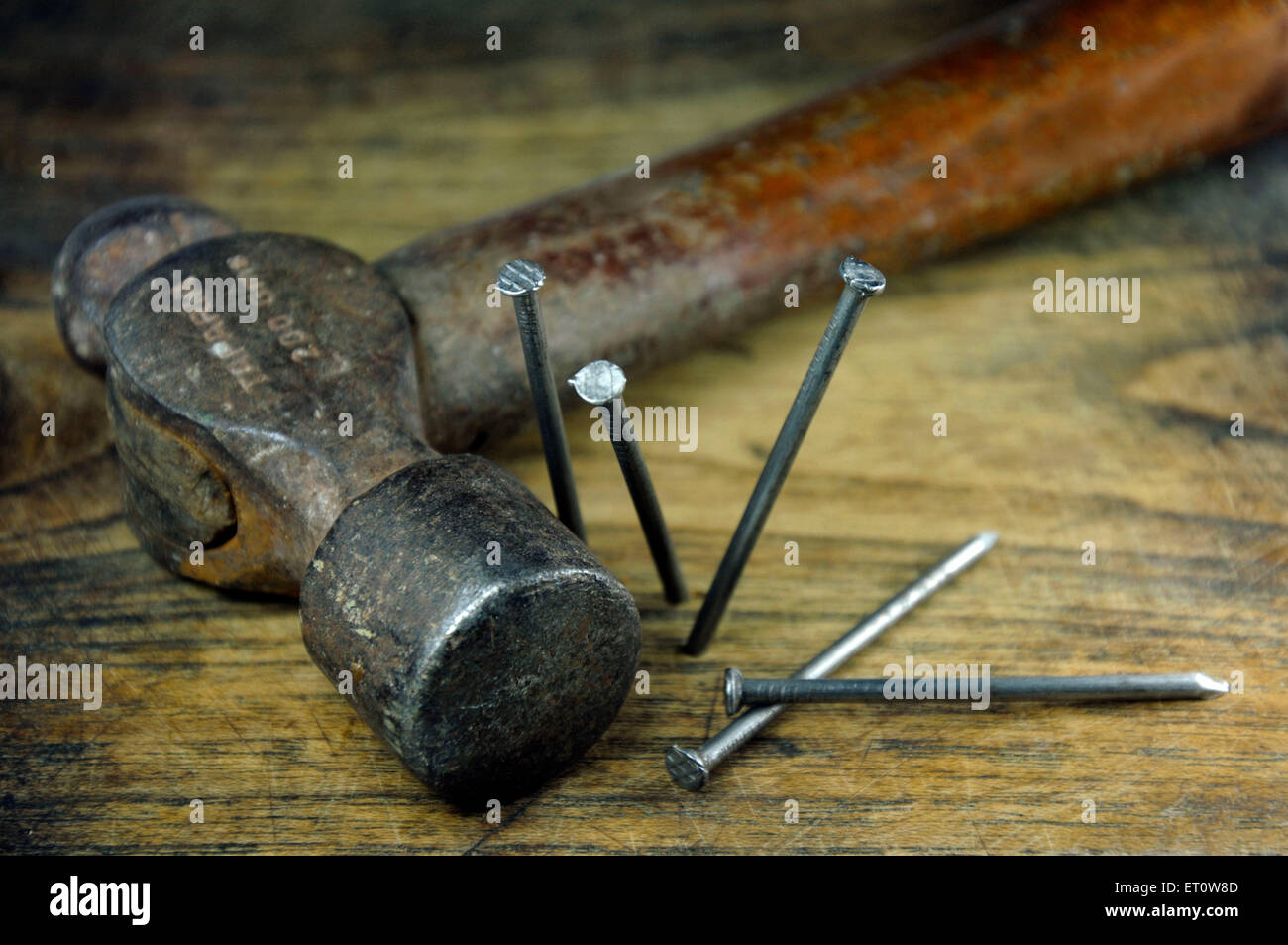 Hammer and nails on wood plank India Asia - Stock Image