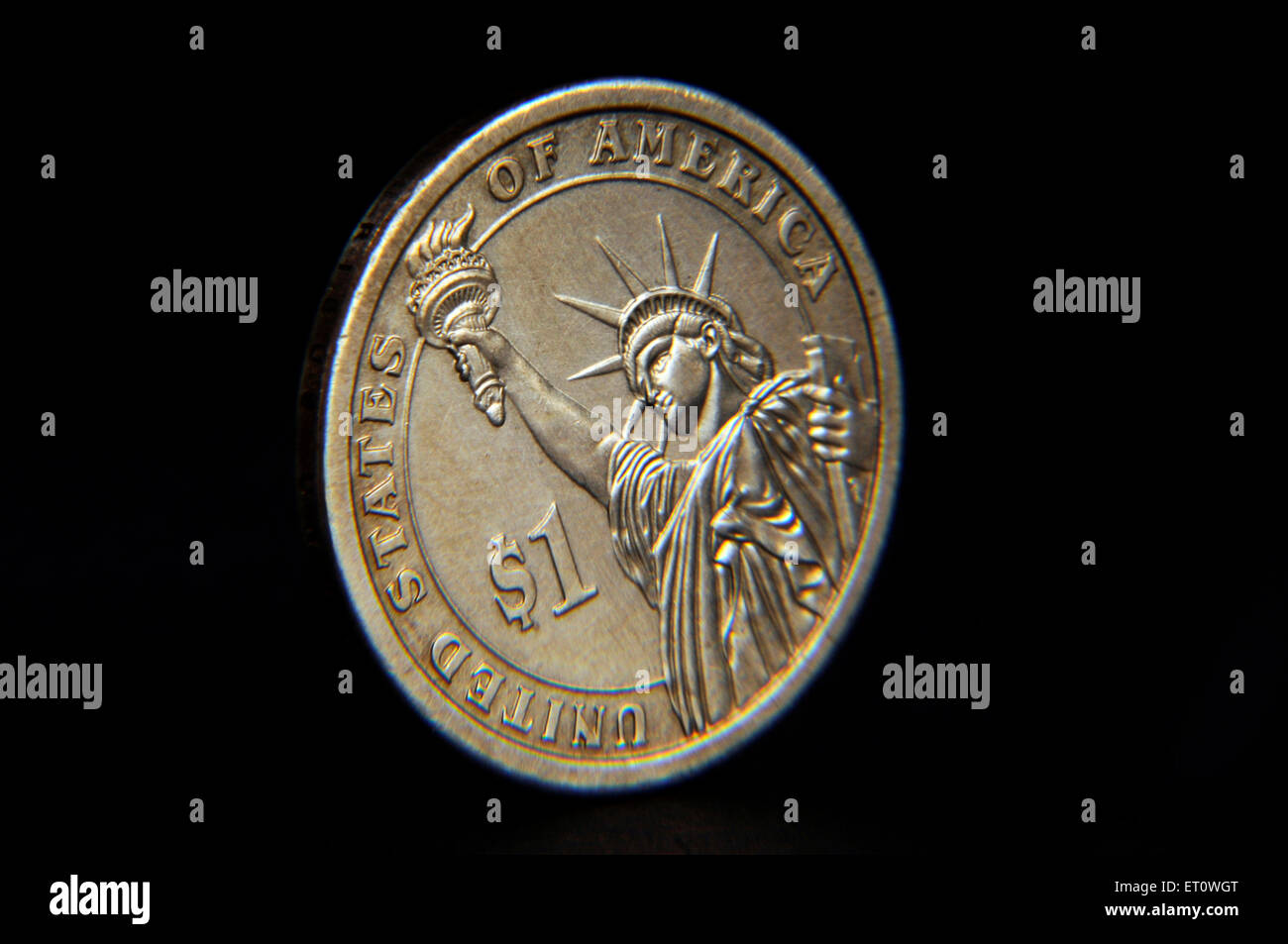 Golden one dollar coin isolated on black - Stock Image