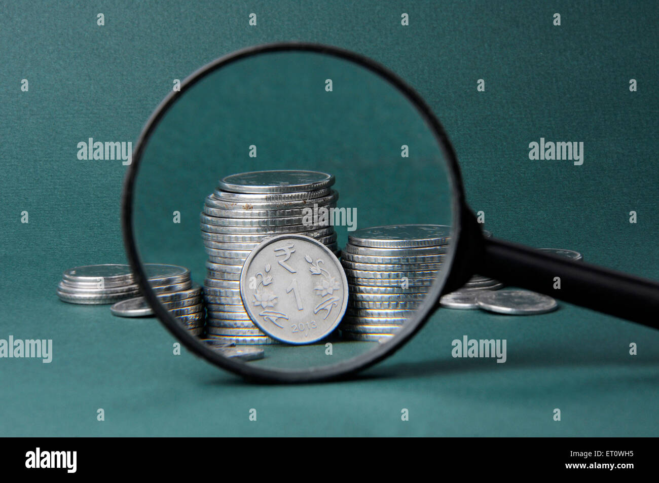 concept of Magnifier and coin - Stock Image
