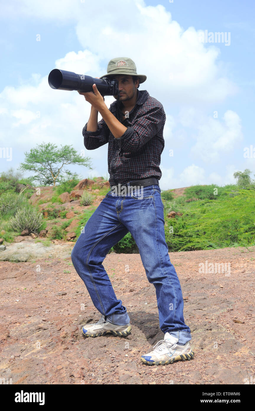 Photographer giving pose while photo shoot ; India Mr#786 - Stock Image
