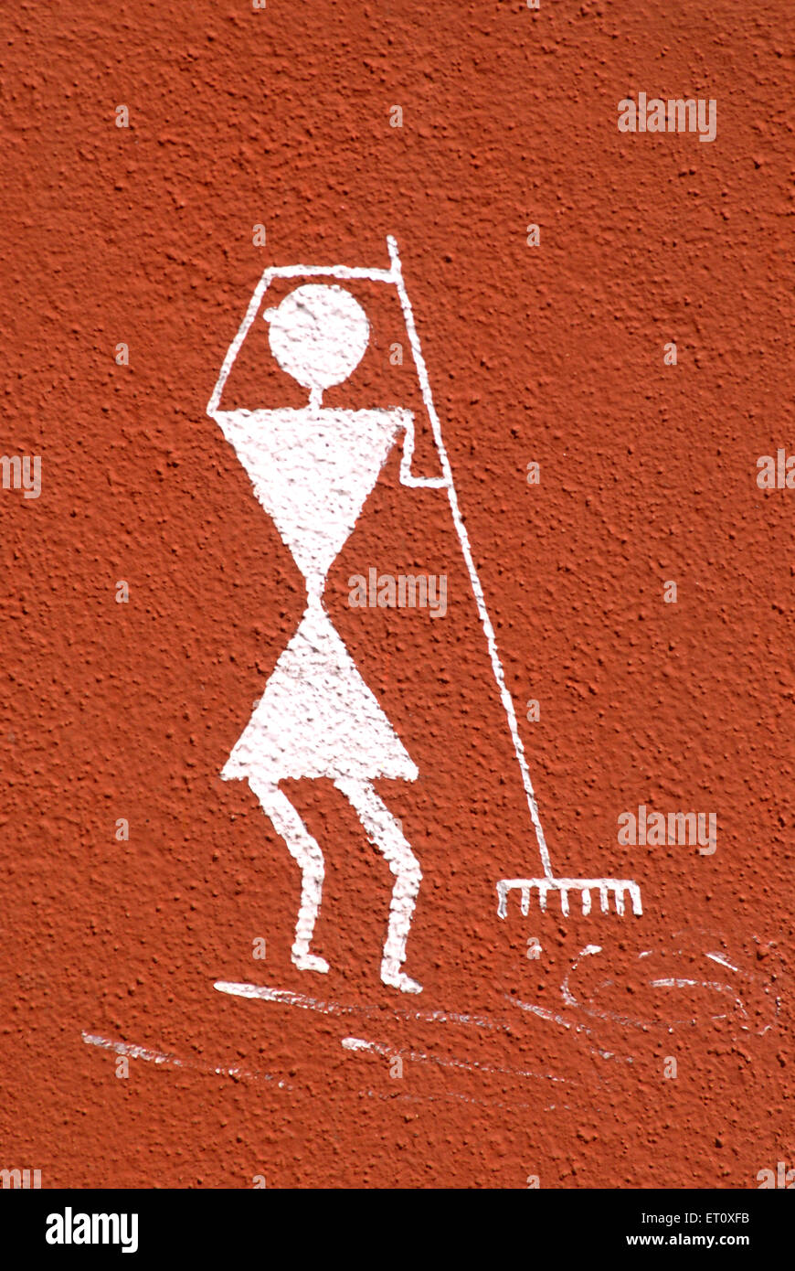 Girl cleaning grass ; Warli painting on wall ; tribal art at top of Parvati hill ; Pune ; Maharashtra ; India - Stock Image