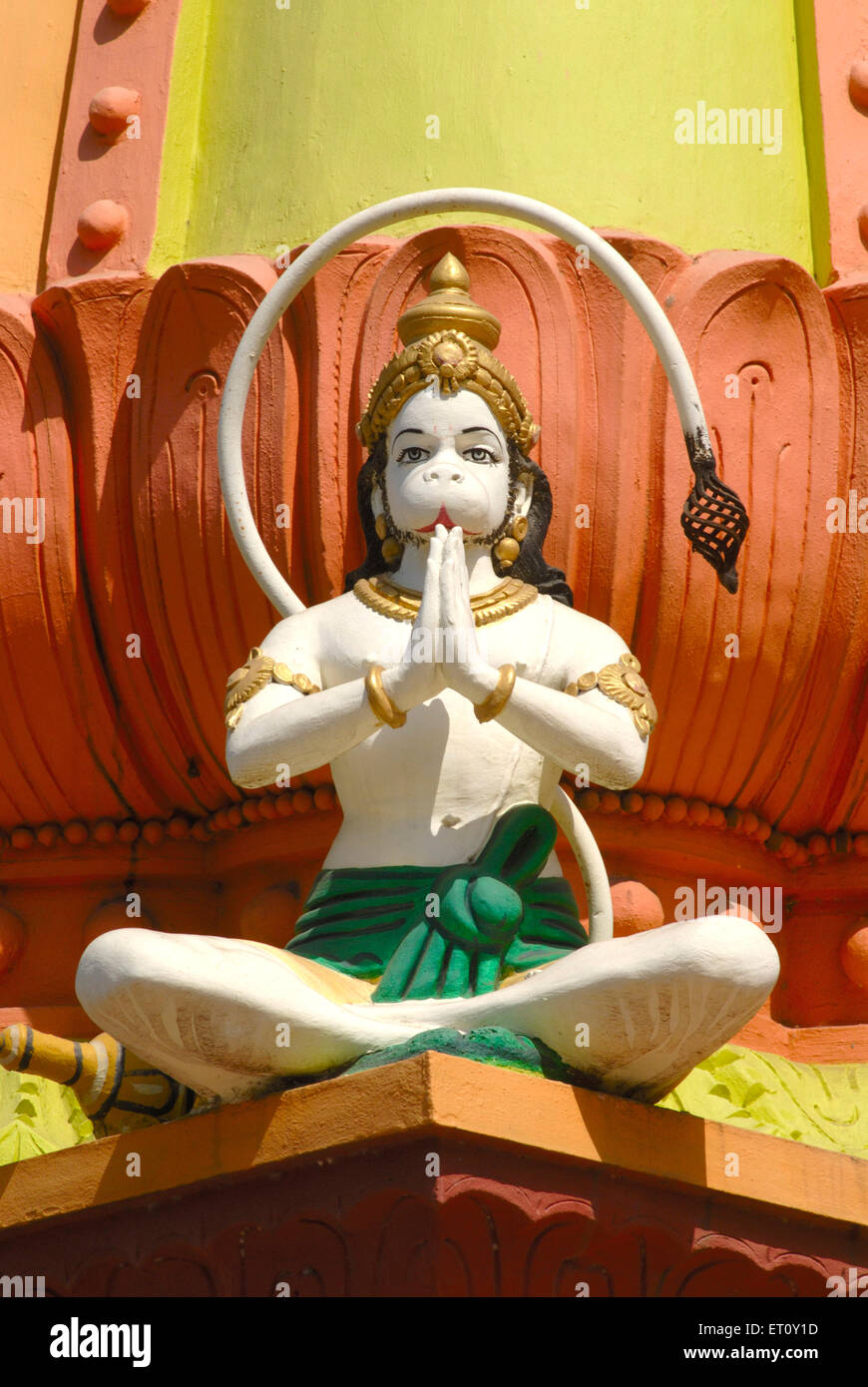 Colourfully painted stucco figure lord Hanuman sitting Namaskar posture ; monkey god ; Maruti temple foothill Parvati - Stock Image