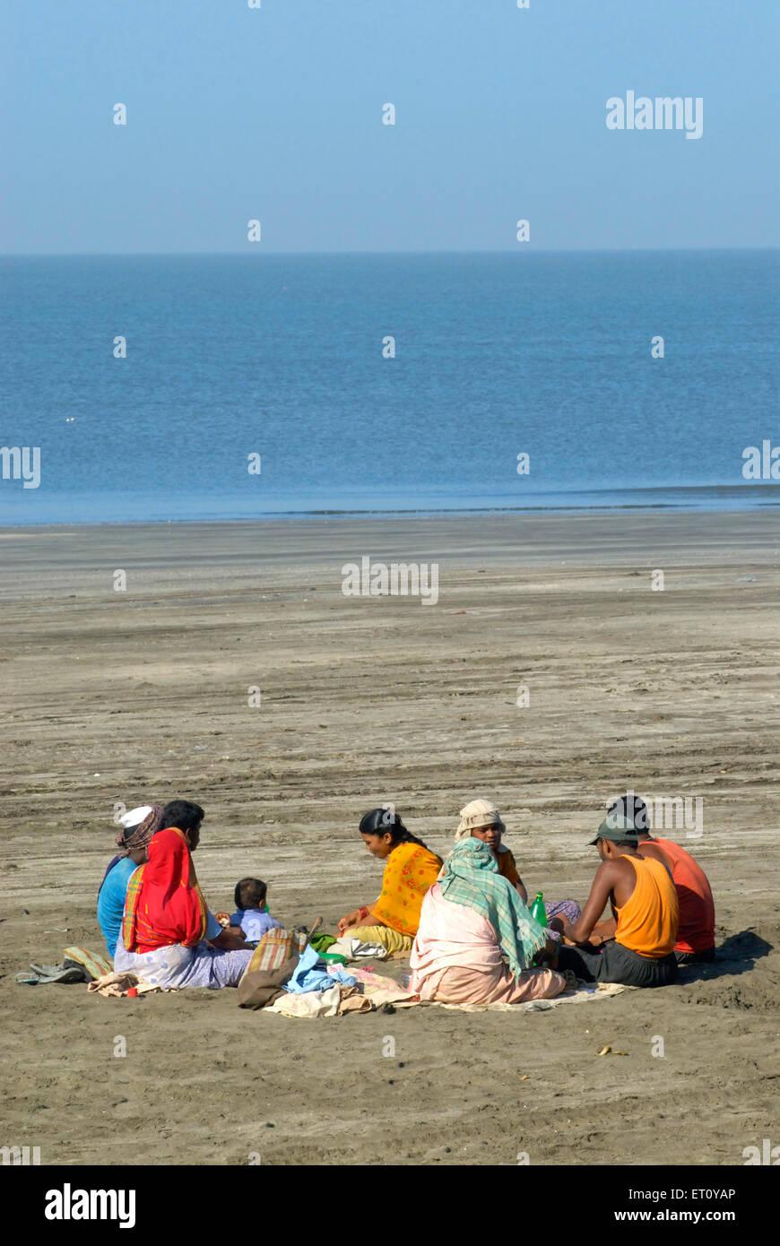 Labourers sitting on sand in round having lunch Arabian sea behind at Kalamb beach ; Bassein Vasai ; District Thane - Stock Image