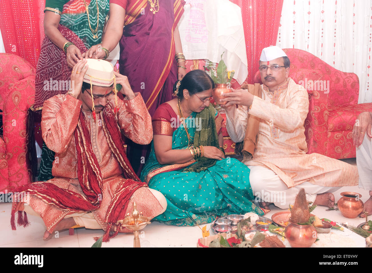 Bridegroom sitting with parents in marriage ceremony MR#778F Stock Photo