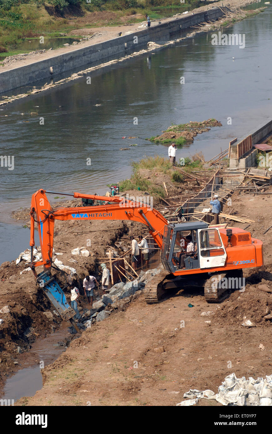 Excavator and digger Bulldozer of TATA HITACHI EX 200 LC heavy machinery ;  excavation work at bank of river Mutha - Stock Image