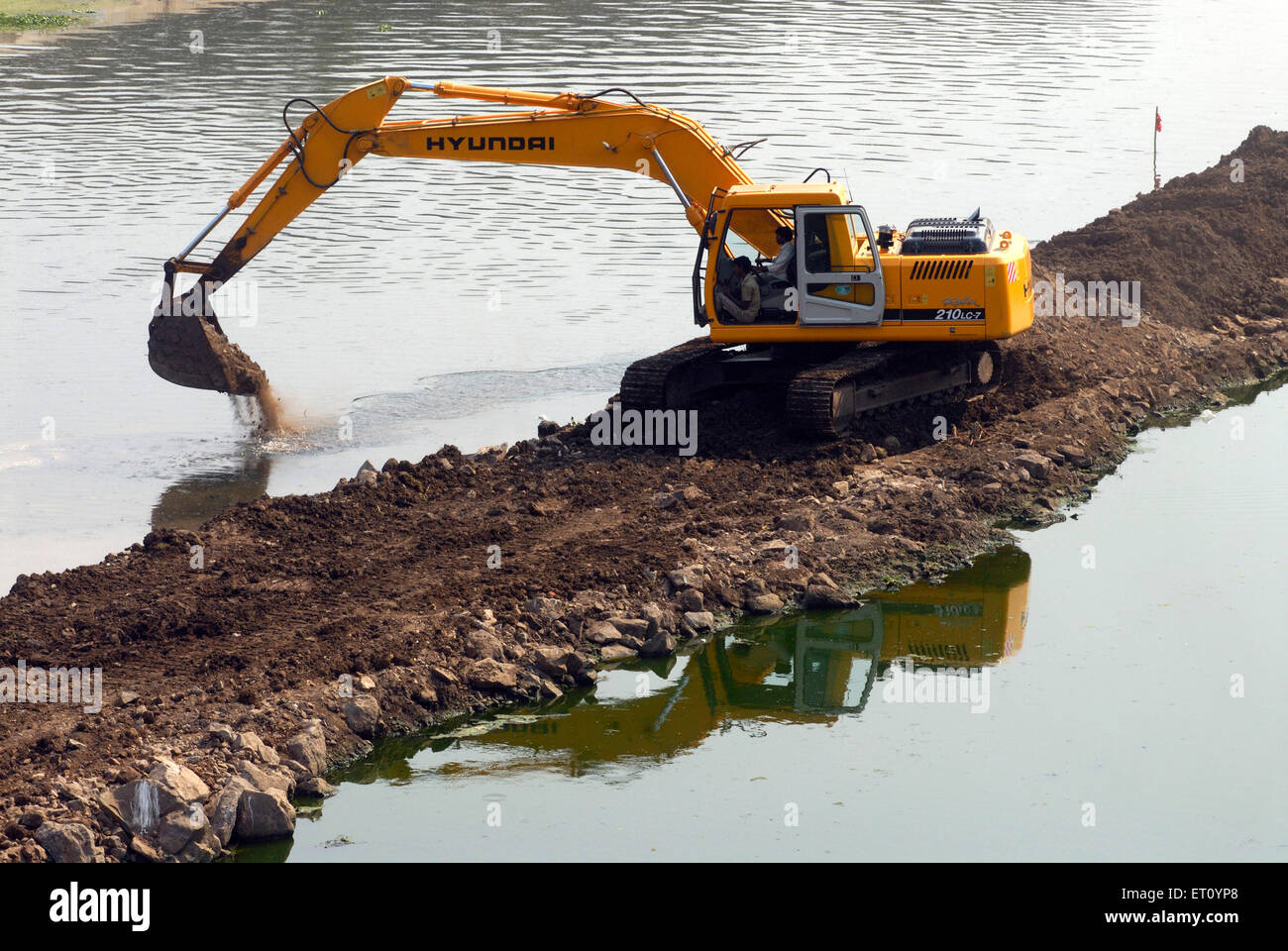 Excavator and digger Bulldozer of HYUNDAI Rolex 210 LC 7 heavy machinery ;  excavation work at bank river Mutha - Stock Image