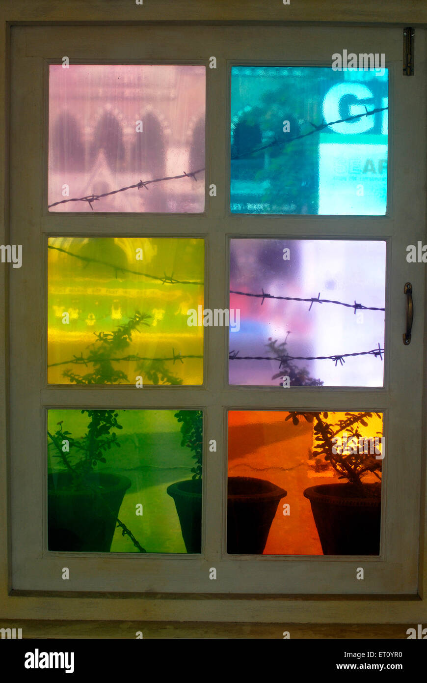 Window with colourful tinted glasses and earthen flower pots at Kala Ghoda art festival 2009  ; Bombay - Stock Image