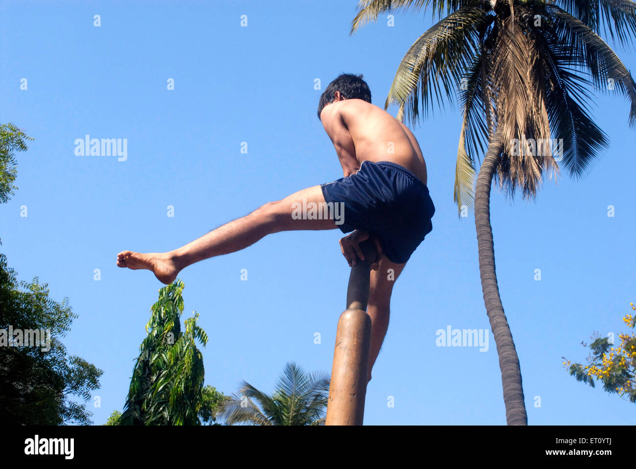 Malkhamb young boy performing gymnastics ; Thane ; Maharashtra ; India 2009 - Stock Image