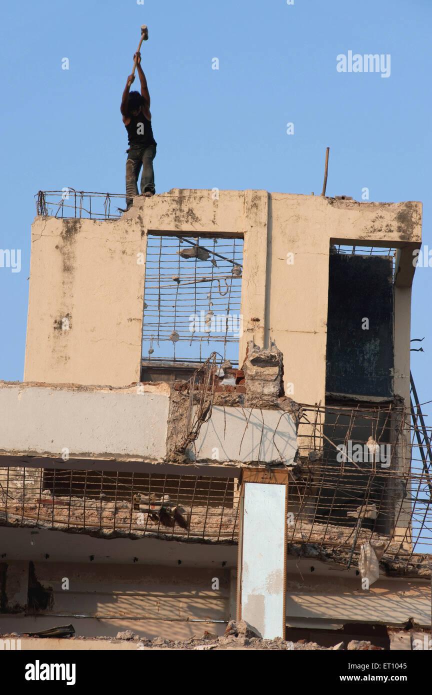 Labor breaking wall of building ; Bombay Mumbai ; Maharashtra ; India 2010 - Stock Image
