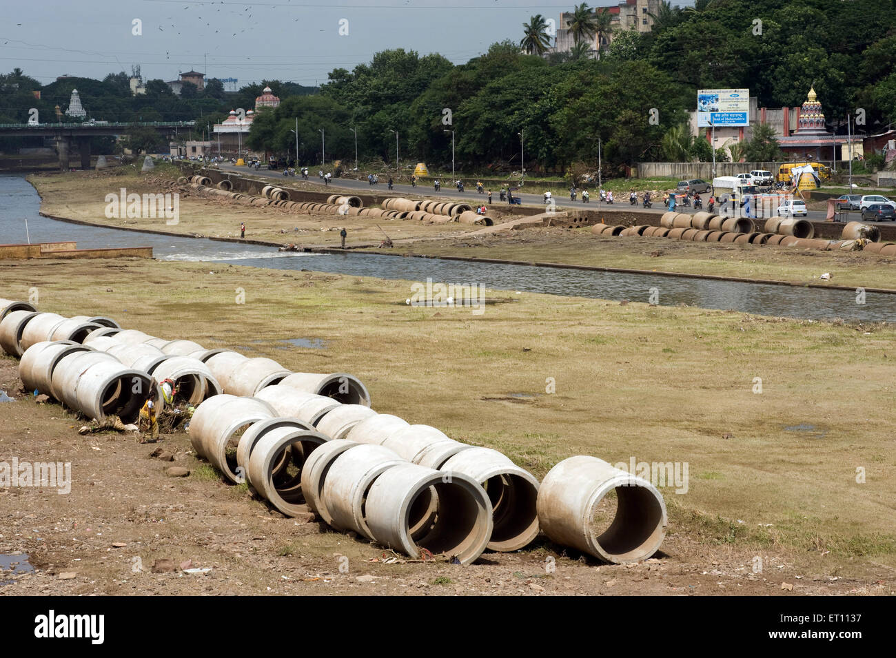 Concrete Hume pipes kept on banks of Mutha River at Pune Maharashtra India Asia 2011 - Stock Image