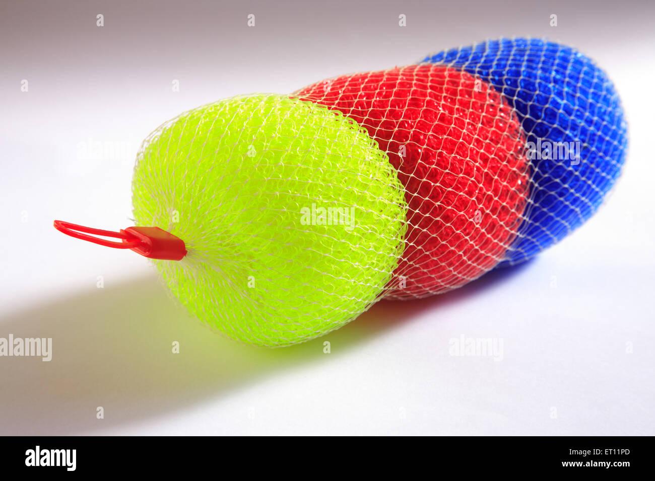 Colourful nylon scouring brush on white background - Stock Image