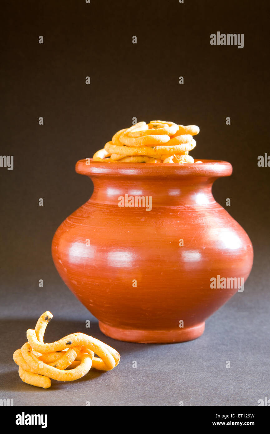 Snack ; murukku in pitcher on black background 3 March 2010 - Stock Image