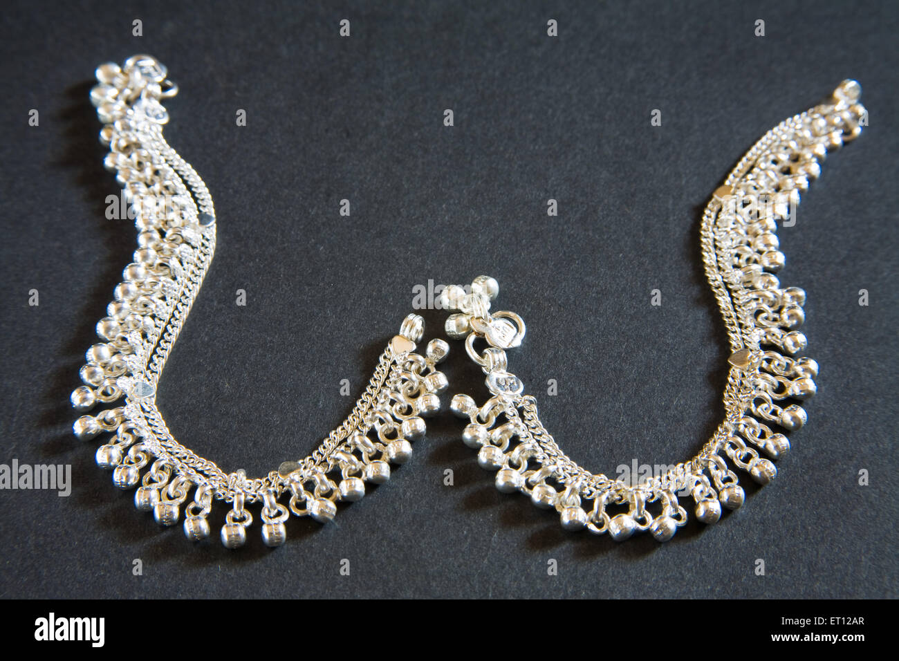 Concept ; silver anklets pair on black background 12 March 2010 - Stock Image