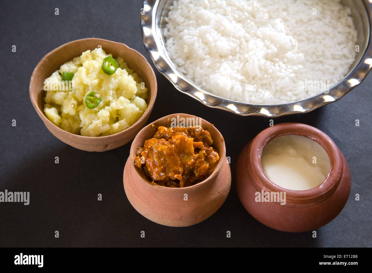 Indian lunch pakhala rice in steel bowl and pickle mash potato with chillies yoghurt in earthen pot black background - Stock Image