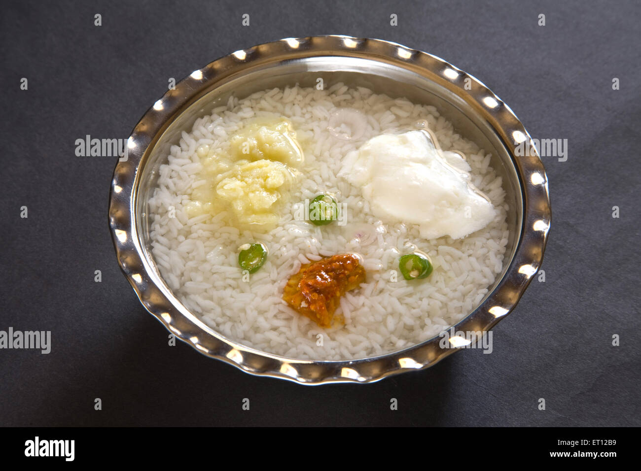 Indian lunch pakhala rice pickle mash potato with chillies and yoghurt in steel bowl on black background 15 April - Stock Image