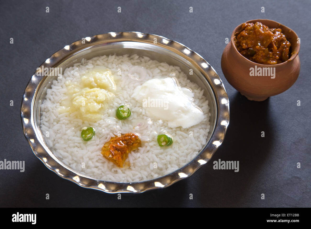 Indian lunch pakhala rice pickle mash potato with chillies and yoghurt in steel bowl with pickle in earthen pot - Stock Image