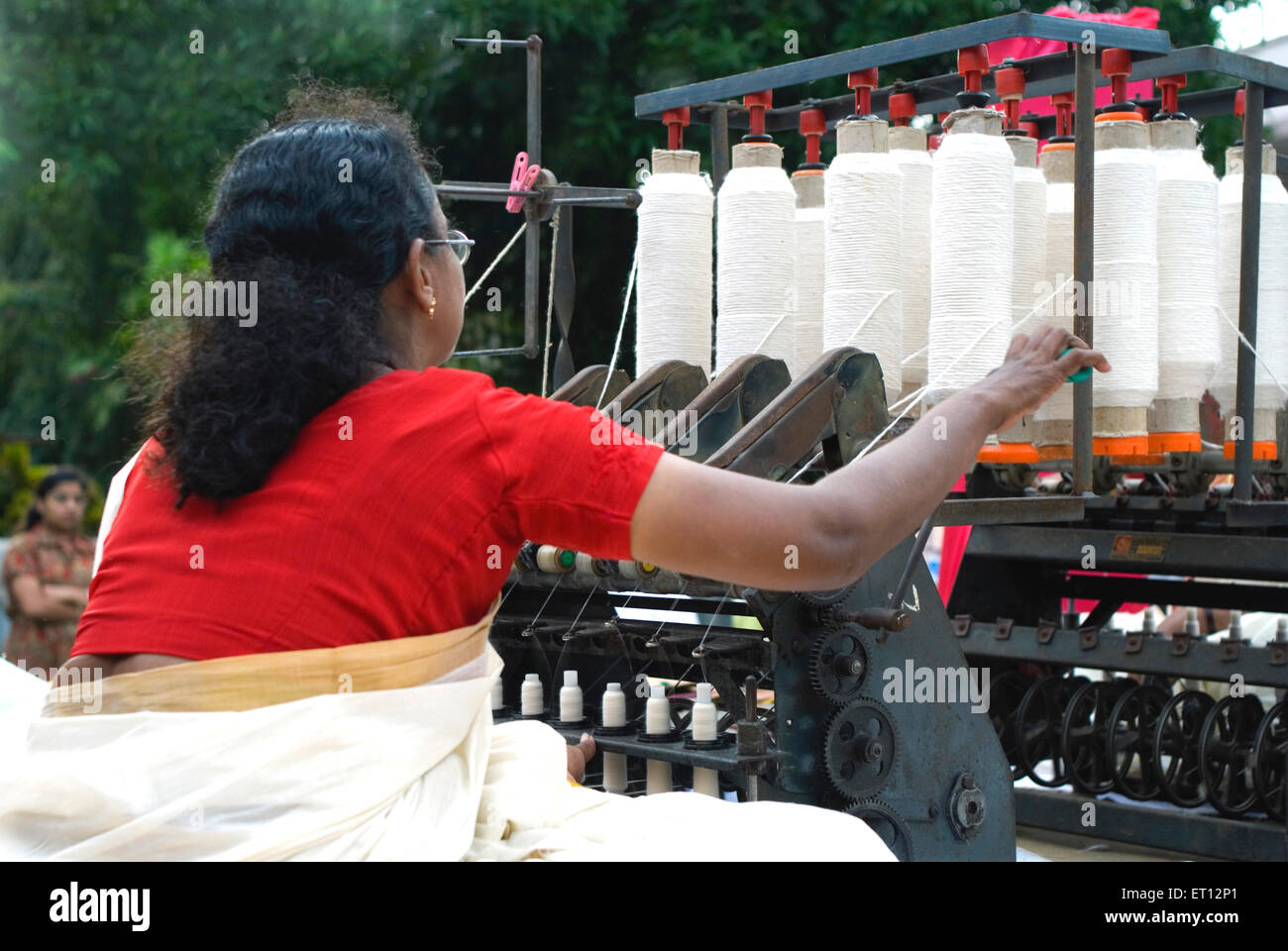 Lady spinning loom making cotton threads ; Trivandrum ; Kerala ; India - Stock Image