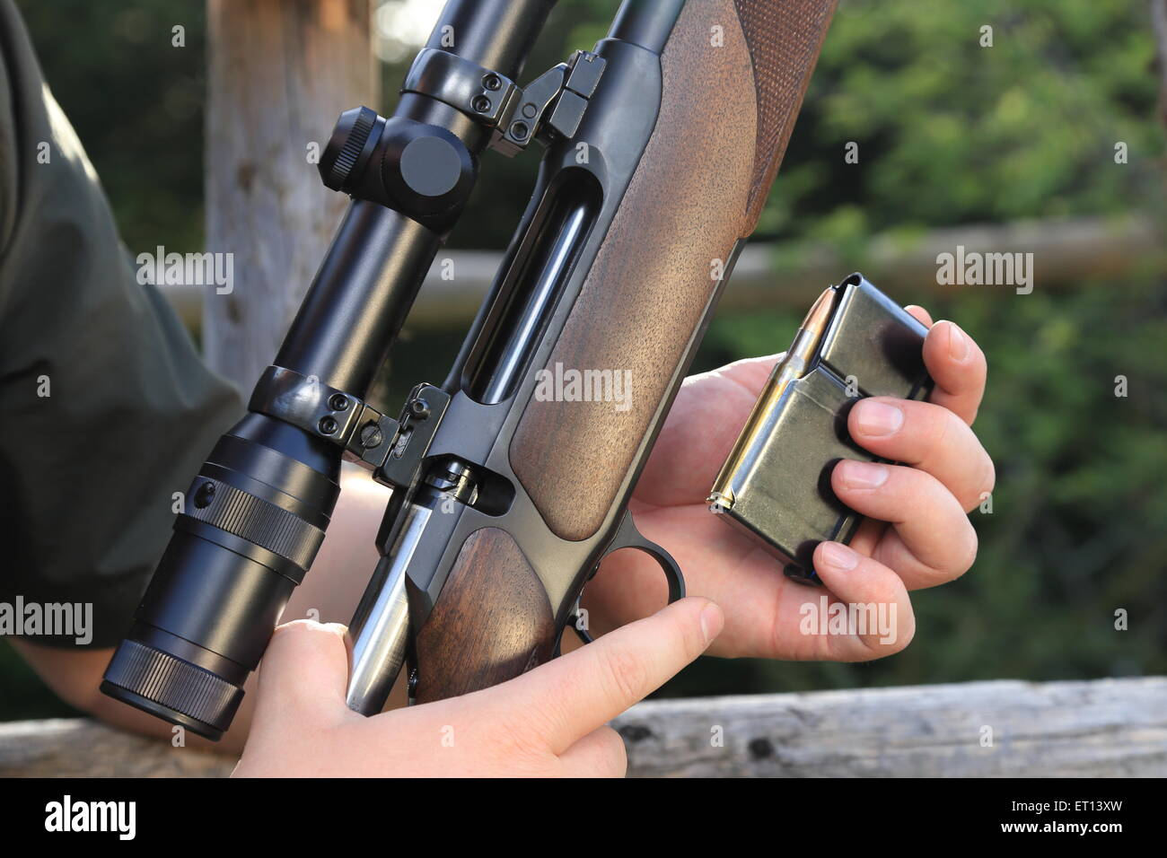 A Hunter loading his hunting rifle gun with magazine - Stock Image